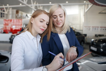 Woman stay a car insurance policy, the agent is pointing at the document Stock Photo