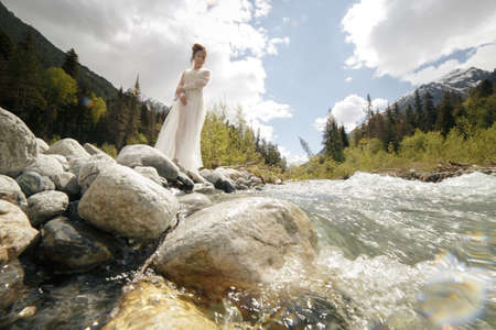 Beautiful boudoir sexy Bride in bathrobe dress. young girl fashion Stylish with bouquet on the nordic Karelian nature landscape background forest Waterfall river i Stock Photo
