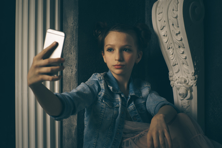 Teen girl excessively sitting at the phone at home. he is a victim of online bullying Stalker social networks Stock Photo - 101260534