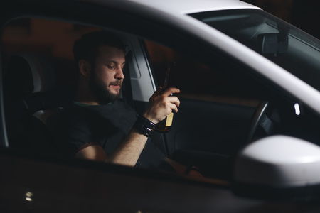 Man drink beer while driving at night in the city dangerously, left hand drive system Stock Photo