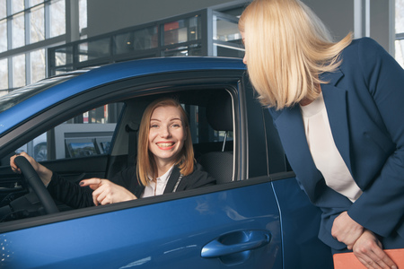 auto business, car sale, consumerism and people concept - happy woman with car dealer in auto show or salon Stock Photo