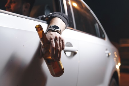 Drunk young man drives a car with a bottle of beer. This is a campaign picture of Dont Drink for Drive. Archivio Fotografico