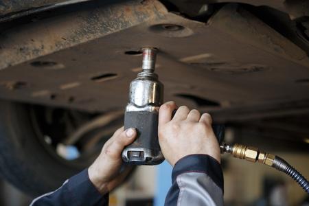 Profecional car mechanic changing motor oil in automobile engine at maintenance repair service station in a car workshop. Reklamní fotografie