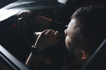 A young handsome bearded man with a bottle of beer or a low-alcohol drink at the wheel of a car. Driving in a state of intoxication