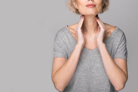 Mujer comprobando la glándula tiroides por sí misma. Cerca de mujer en camiseta blanca tocando el cuello con una mancha roja. El trastorno de la tiroides incluye bocio, hipertiroidismo, hipotiroidismo, tumor o cáncer. Cuidado de la salud. Foto de archivo