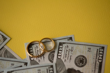 Golden wedding rings on dollars bill background. Divorce or infidelity