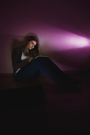 Sad teenage girl sitting near laptop in dark room. She is a victim of online bullying Stalker social Stock Photo - 113851236
