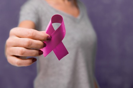 Elderly woman holding purple ribbon awareness w copy space. Symbol is used to raise awareness for Alzheimers disease, elder abuse, epilepsy, pancreatic cancer, thyroid cancer and lupus. Stock Photo