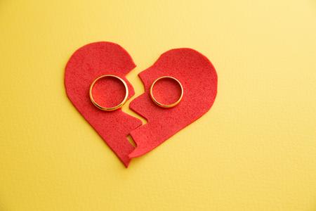 Anillos de boda en la figura de un corazón roto de un árbol, martillo de un juez sobre un fondo de madera. Divorcio Foto de archivo