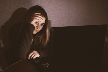 Teen girl excessively sitting at the computer laptop at home. he is a victim of online bullying Stalker social networks.Too much work sleepy stressed young woman