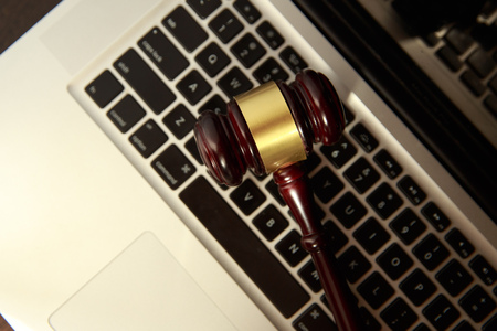 Online auction concept. Auction or judge gavel on a computer keyboard. Judge hammer on laptop computer
