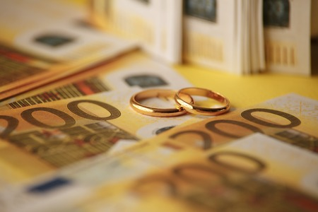 Two wedding rings and money as symbol for an expensive alliance. Golden wedding rings on euro banknotes