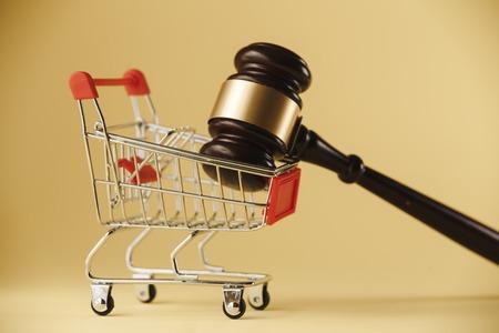 Protección de los derechos del consumidor. Martillo del juez con un carro sobre un fondo blanco. De cerca Foto de archivo