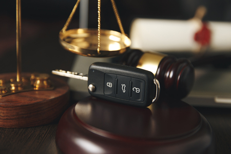 Closeup of a judges gavel and the keys to the car over the soundboard