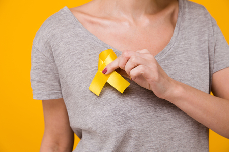 Young female holding yellow gold ribbon awareness symbol for endometriosis, suicide prevention, sarcoma bone cancer, bladder cancer, liver cancer and childhood cancer concept. Stock Photo - 113850182