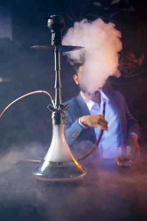 Ton-Shisha-Schüssel mit handwerklichem Tabak und glühender Kokosnussspule mit schwarzem Hintergrund des Shisha-Rauchs isoliert. Shisha rauchen auf Party