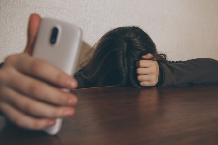 Teen girl excessively sitting at the phone at home. he is a victim of online bullying Stalker social networks - Image Stock Photo - 113849497