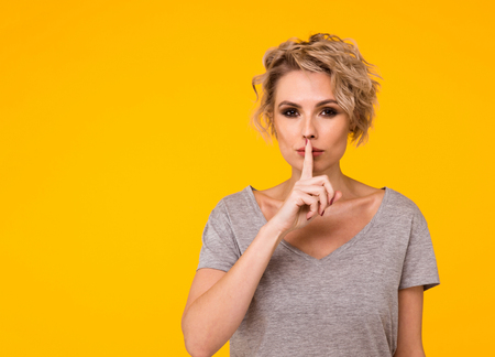 Silence. Woman asking for silence or secrecy with finger on lips hush hand gesture yellow background wall. Pretty girl placing fingers on lips, shhh sign symbol. Negative emotion facial expression