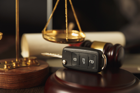 Close up of judge gavel and car keys over