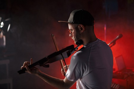 Close-up photo of man playing electric violin Stock Photo