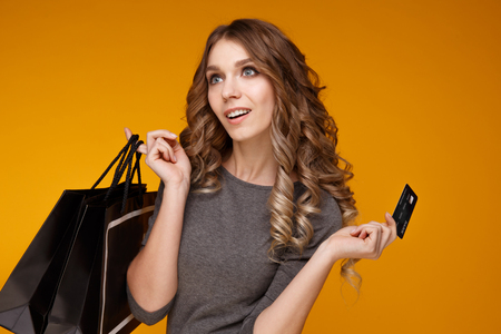 lose-up portrait of happy young brunette woman holding credit card and colorful shopping bags, looking at camera, isolated on yellow background