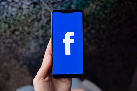 Tula, Russia - November 28, 2018: Facebook social media app logo on log-in, sign-up registration page on mobile app screen on smart devices in business persons hand at