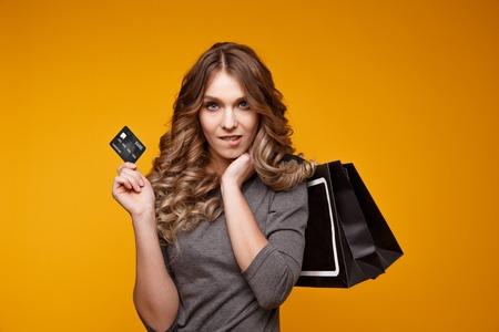 Los-up portrait of happy young brunette woman holding credit card et sacs colorés, looking at camera, isolé sur fond jaune