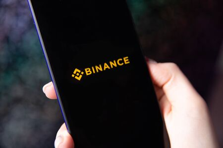 Tula, Russia - November 28, 2018: Apple iPhone and Binance logo and bitcoin, ethereum and dollars. is a cryptocurrency exchange. Editorial