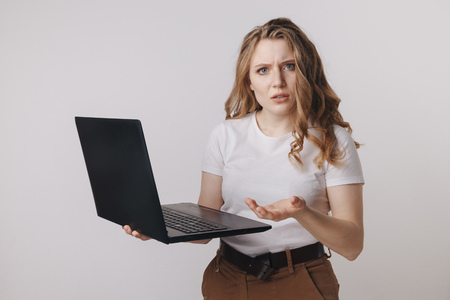 Young businesswoman at modern home office desk with laptop impressed by the bill to pay, revealed online affair, e-mail about broken romantic relationship, photo partner being unfaithful,