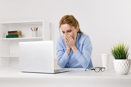 Exited woman surprised by something watching her laptop at office.