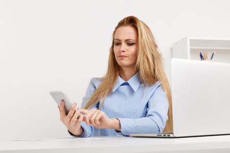 Picture of angry office worker having problems with phone.