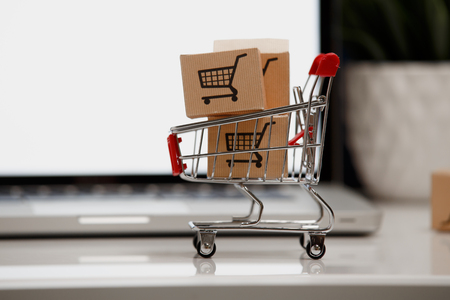 Many paper boxes in a small shopping cart on a laptop keyboard. Concepts about online shopping that consumers can buy things directly from their home or office just using a few clicks via web browser. 版權商用圖片 - 118150769