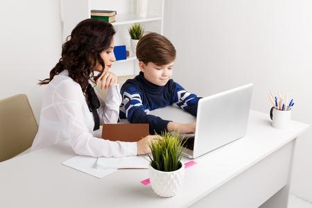 Doing homework on the laptop. Child doing homework and his teacher helps.