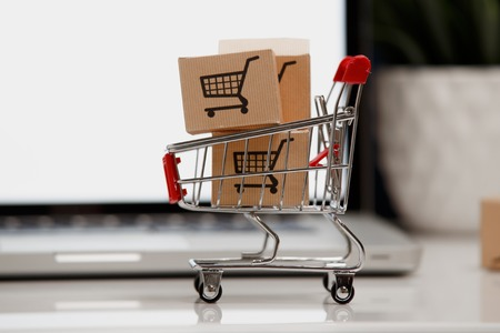 paper boxes in a shopping cart on a laptop keyboard. Concepts about online shopping that consumers can buy things directly from their home or office just using a few clicks via web browser.