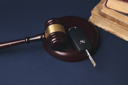 Close up of judge gavel and car keys over soundboard on white background Stock Photo