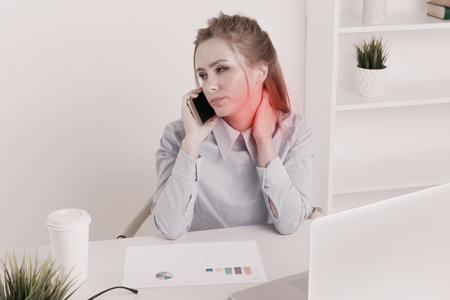 Office woman sitting infront of the computer at her workplace and feeling neckache. Sad worker feeling upset and tired.