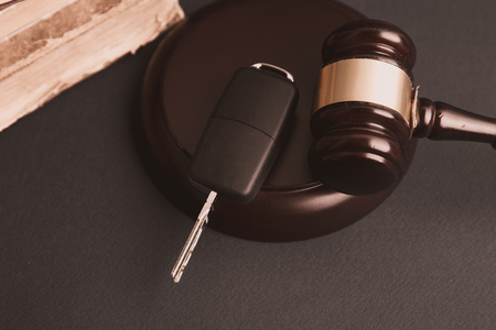 Close up of judge gavel and car keys over soundboard on white
