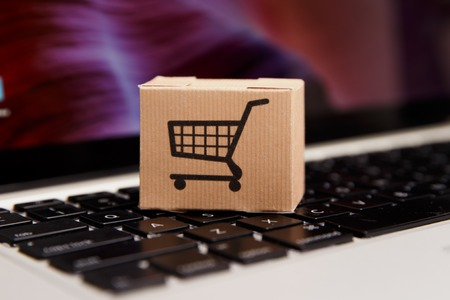 Online shopping . ecommerce and delivery service concept : Paper cartons with a cart or trolley logo on a laptop keyboard, depicts customers order things from retailer sites Фото со стока