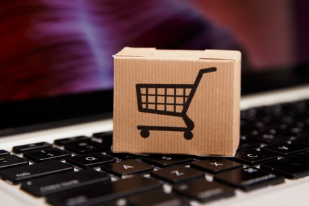 Online shopping . ecommerce and delivery service concept : Paper cartons with a cart or trolley logo on a laptop keyboard, depicts customers order things from retailer sites Stock Photo