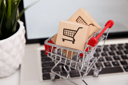 Many paper boxes in a small shopping cart on a laptop keyboard. Concepts about online shopping that consumers can buy things directly from their home or office just using a few clicks via web browser. Stock Photo - 119192631
