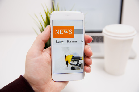 Online news in mobile phone. Close up of smartphone screen. Man reading articles in application. Hand holding smart device. Mockup website. Newspaper and portal on internet