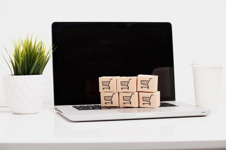 Online shopping ecommerce and delivery service concept : Paper cartons with a shopping cart or trolley logo on a laptop keyboard, depicts customers order things from retailer sites via the internet Stock Photo - 119193259