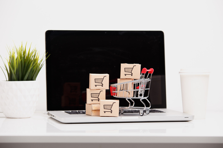 Online shopping ecommerce and delivery service concept : Paper cartons with a shopping cart or trolley logo on a laptop keyboard, depicts customers order things from retailer sites via the internet