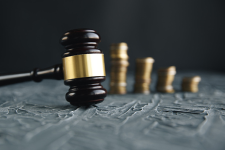 Judges Hand Holding Gavel Over Stacked Golden Coins