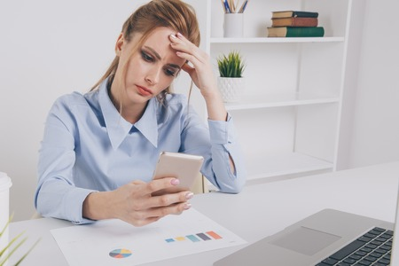 Young office girl sitting at her workplace feeling bad. Woman has a headache. Looking tired. Phone problems. Stockfoto