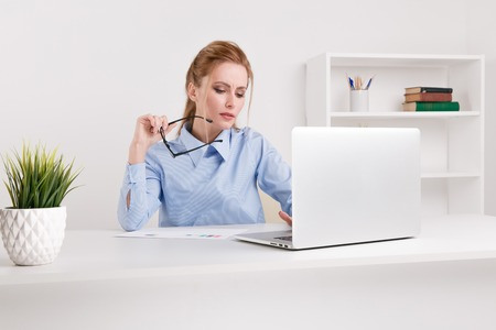 Serious woman holding the glasses working her laptop. Office woman looks tired.