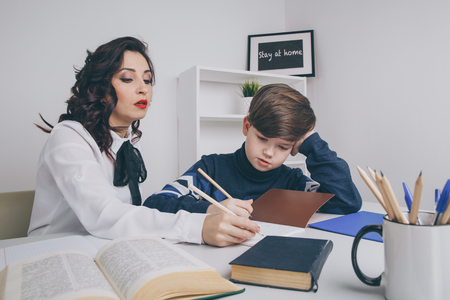 Young teacher trying to explain information to the boy. Educating together. Stock Photo