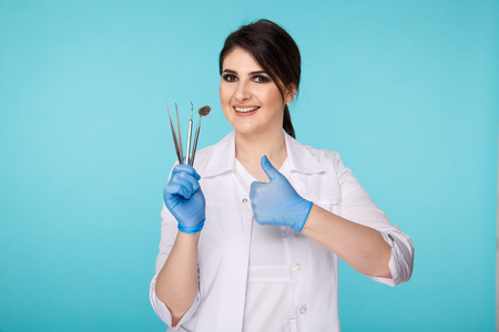 Handsome brunette dentist with tools isolated over the blue background.