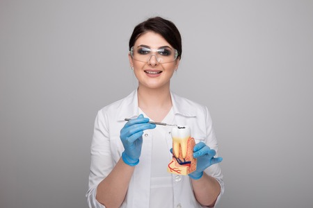 Female dentist with tools on grey background.