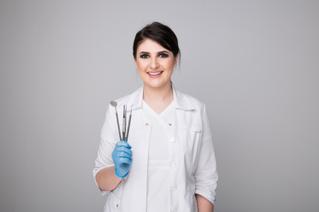 Female dentist with tools on grey